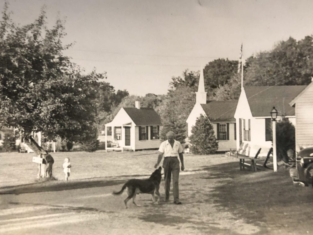 Herbert Plimpton playing with a dog in front of New England Village